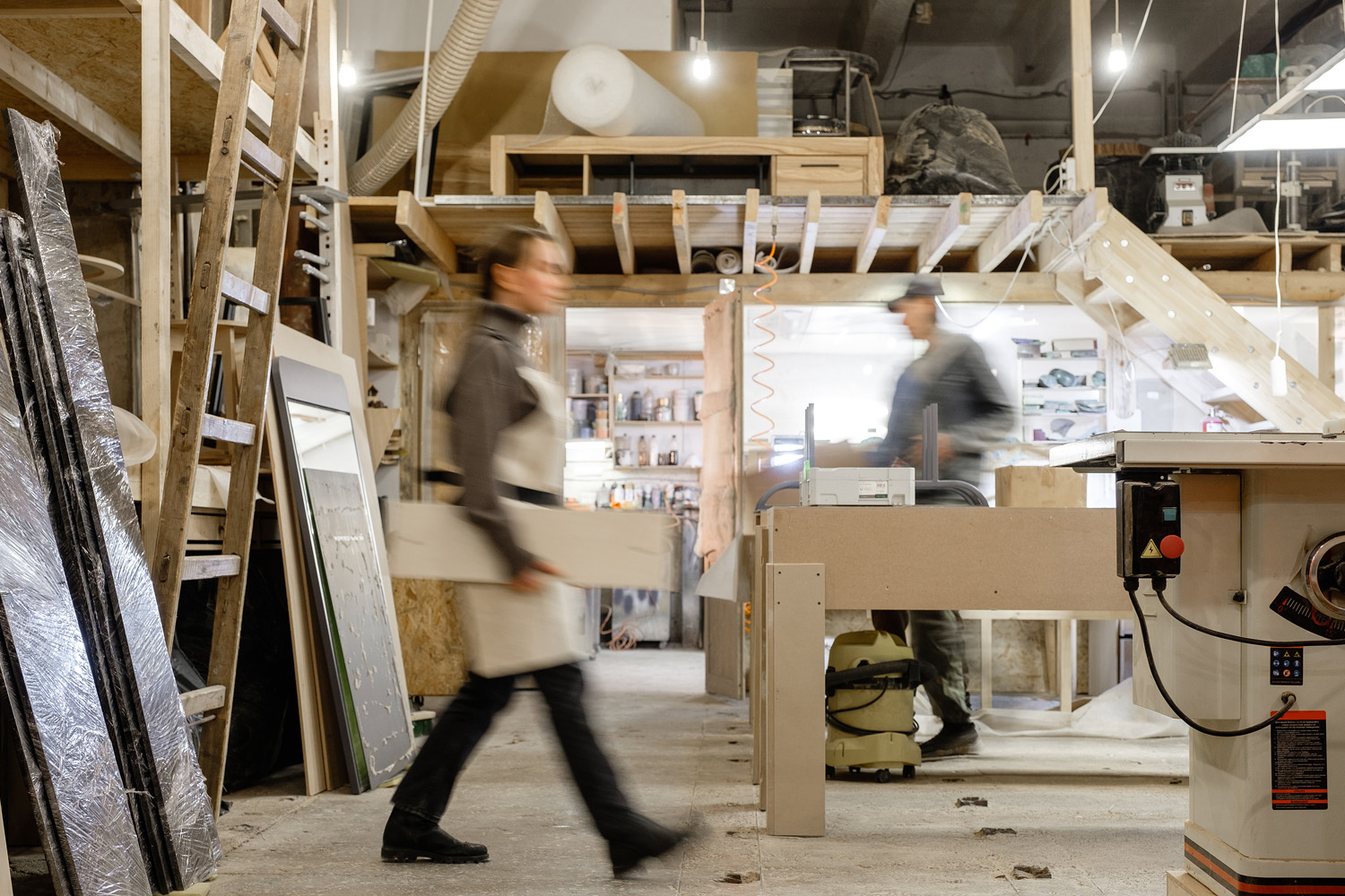 Exposure photography two unidentified young employees of small woodworking and furniture industry working on new furniture collection. Concept of own small successful production